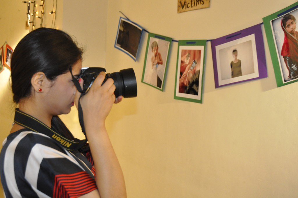 Student is taking photograph in an exhibition organized by Media Studies Department.